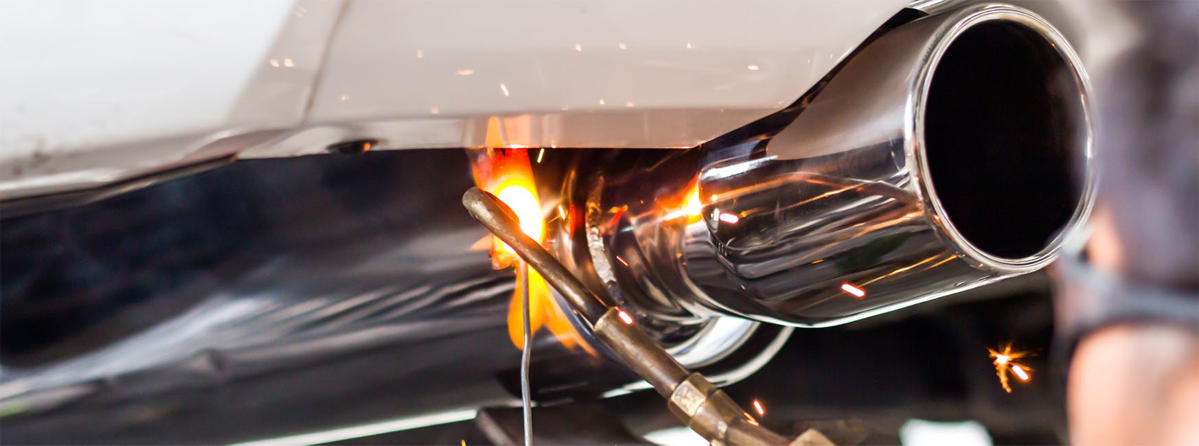 custom muffler installation with flame at denver based buds muffler service